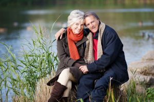 21167760 - a happy senior couple posing by the lake